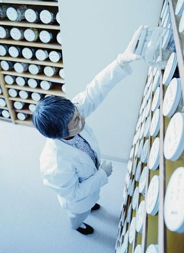 Woman Selecting a Jar of Herbal Medicine : Stock Photo