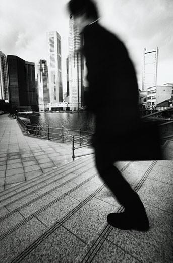 Businessman Running Down Sidewalk : Stock Photo