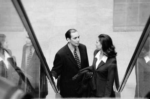 Stock Photo: 1598R-188045 Two businesspeople riding escalator, elevated biew (B&W)