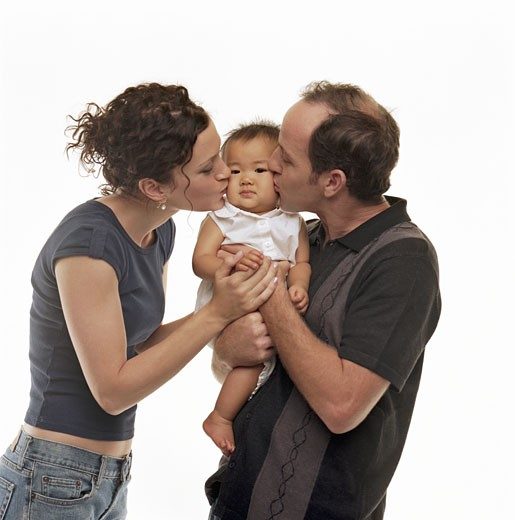 Couple kissing checks of adopted baby girl (9-12 months), portrait : Stock Photo