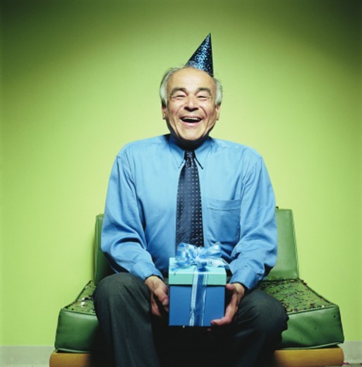 Stock Photo: 1598R-19289 Mature man with party hat holding present, laughing