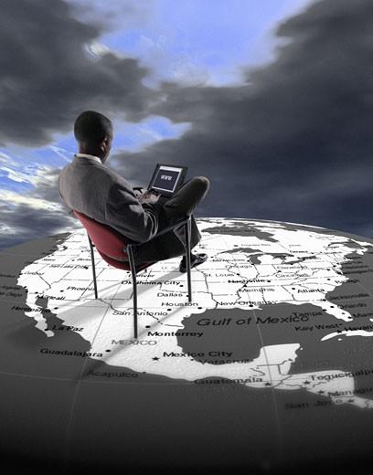 Businessman Sitting on a Globe Using a Laptop : Stock Photo