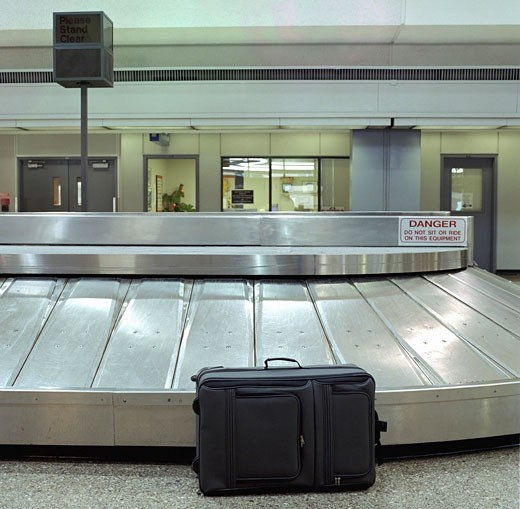 Unattended suitcase sitting in baggage claim at airport : Stock Photo