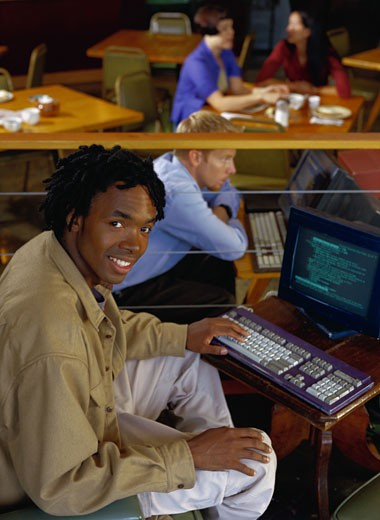 Smiling Man at a Cybercafe Computer : Stock Photo