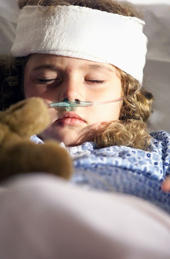 a little caucasian girl lies in a hospital bed recovering from a head injury : Stock Photo