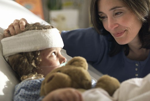 Stock Photo: 1598R-200843 a caucasain mother visits and consoles her young child as she lays recovering in the hospital