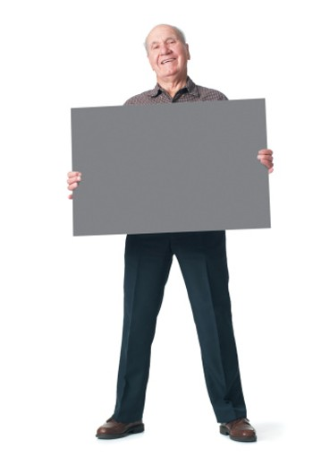 Stock Photo: 1598R-200963 an elderly caucasian man in black pants and a brown shirt holds a sign in front of himself