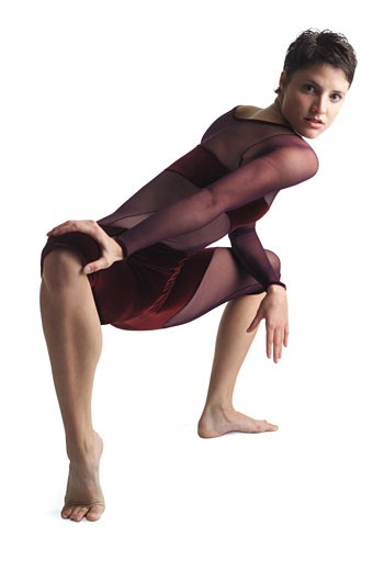 a young caucasian female dancer in a leotard stretches out her legs and contorts her body forward : Stock Photo