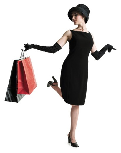 Stock Photo: 1598R-201243 silhouette sophisticated woman in black dress hat as she holds shopping bags and kicks up her foot
