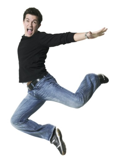 full body shot of a young adult male in a black shirt as he runs and leaps through the air : Stock Photo