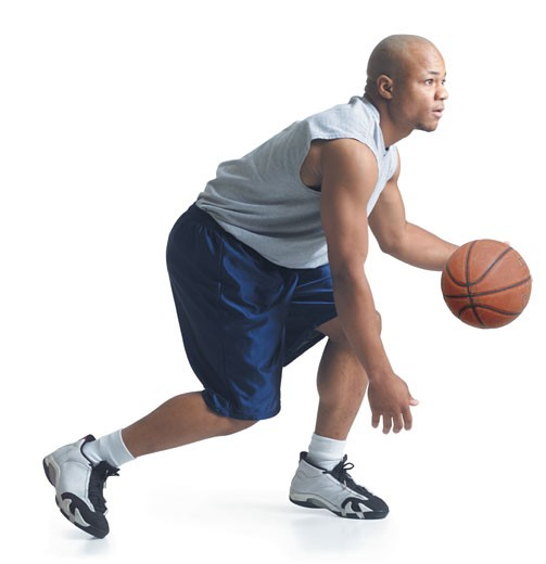 a young african american man wearing blue basketball shorts and a gray tank top is running forward as he dribbles a ball : Stock Photo