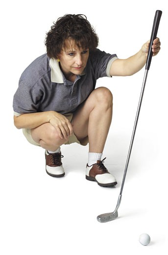 Stock Photo: 1598R-201943 a middle age caucasian female golfer in a stripped shirt crouches down with her putter and lines up a shot