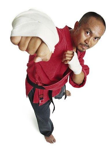 an adult asian male martial arts expert in red punches and looks up at the camera : Stock Photo