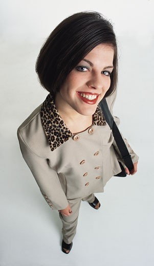 beautiful young caucasian woman with short dark hair dressed in a tan coat with  leopard collar and black purse stands looking into the camera : Stock Photo