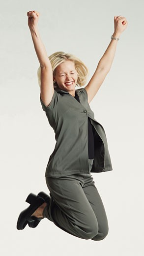 beautiful caucasian woman shoulder length blond hair in gray suit jumps into the air in excitement : Stock Photo