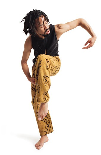 a young african american male modern dancer in yellow pants and a black tank top balances on one leg and curves his arm out : Stock Photo
