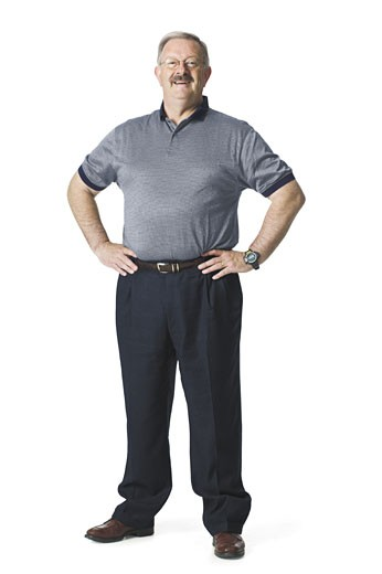 A man with a moustache smiles with his hands on his waist. : Stock Photo