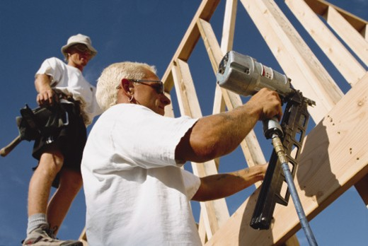 Stock Photo: 1598R-202351 two caucasian construction workers frame a house using a nailgun and hammers