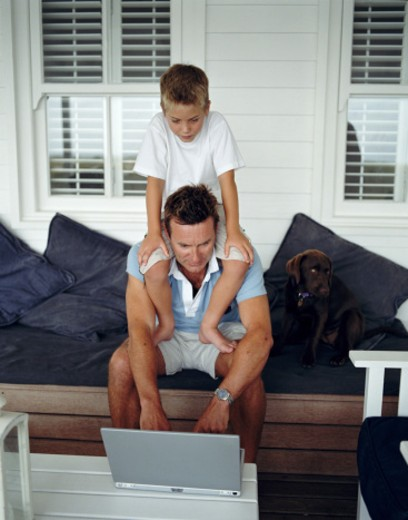 Stock Photo: 1598R-20384 Boy (6-8) sitting on father's shoulders, father using laptop