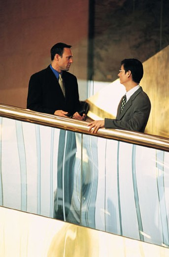 Two businessmen talking by banister : Stock Photo