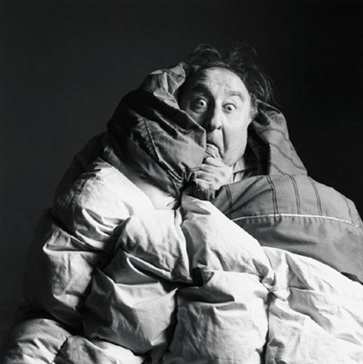 Stock Photo: 1598R-208028 Frightened man with blankets wrapped around himself