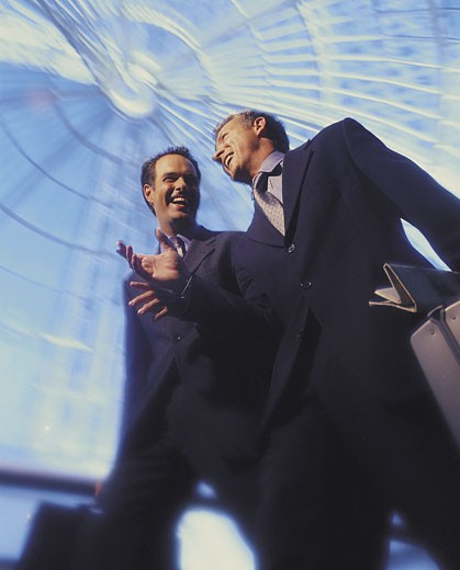Businessmen laughing, walking under glass dome : Stock Photo