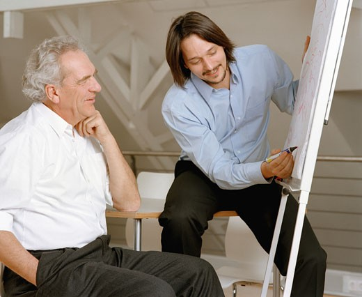 Stock Photo: 1598R-21020 Businessman using drawing board in front of mature man