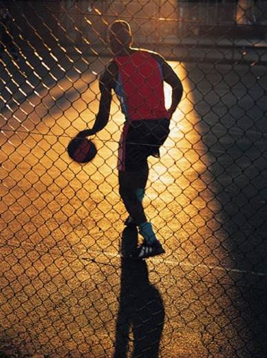 Stock Photo: 1598R-210256 Man dribbling basketball behind fence
