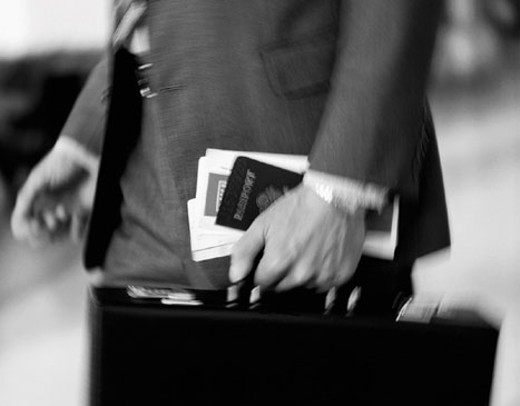 Hand of businessman carrying passport and briefcase : Stock Photo