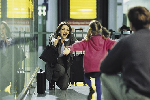 Businesswoman greeting child at airport : Stock Photo