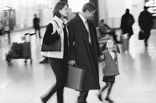 Family with businessman at airport : Stock Photo