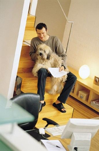 Man breaking from work to pet dog : Stock Photo