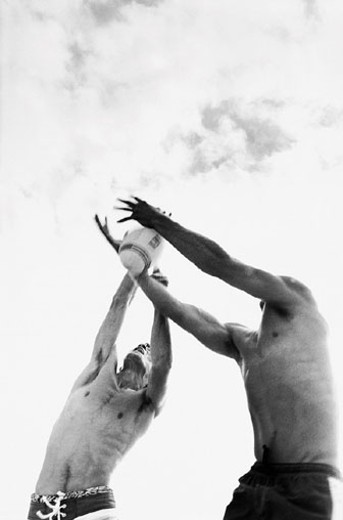 Two men jumping to catch rugby ball : Stock Photo