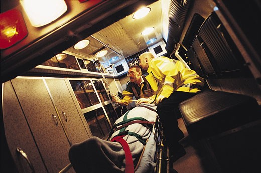 Paramedics treating patient in ambulance : Stock Photo