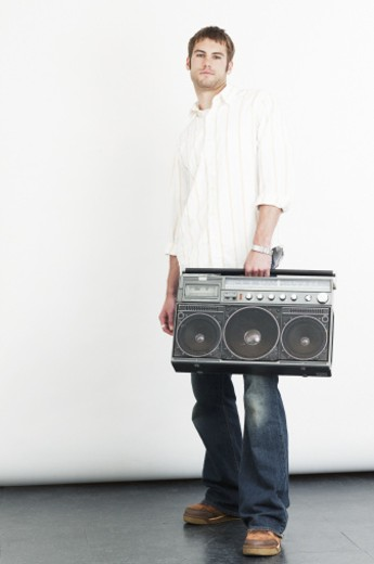 Stock Photo: 1598R-21127 Young man carrying boom box, portrait