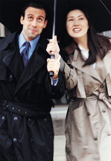 Businessman and Businesswoman Share Umbrella : Stock Photo