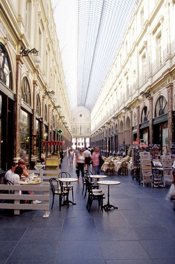 Shoppers sitting and walking in a market, St-Hubert Du Roi De La Reine des Princes, Brussels, Belgium : Stock Photo