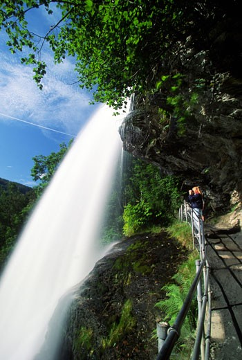Stock Photo: 1598R-213095 Tourist looking at a waterfall, Geiranger, Norway