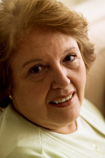 Portrait of a senior woman looking at camera smiling : Stock Photo