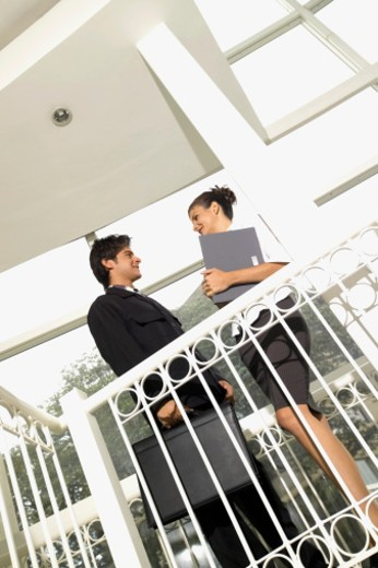 Young businessman and businesswoman standing on balcony outdoors, low angle view : Stock Photo