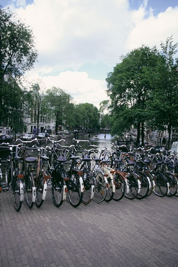 Bicycles parked by a canal, Netherlands : Stock Photo