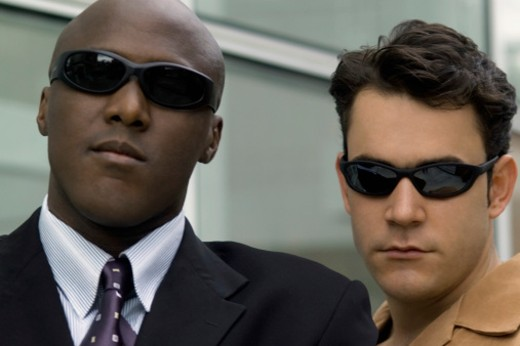 Two businessmen wearing sunglasses and standing outside of office building, close-up : Stock Photo