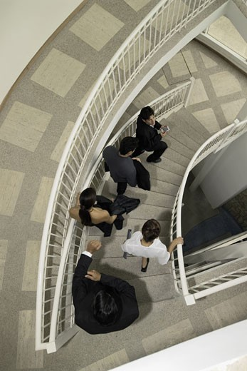Group of businesspeople on spiral staircase, high angle view : Stock Photo