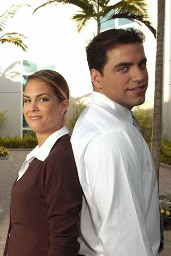 Young Hispanic businessman and businesswoman back to back and smiling outdoors : Stock Photo