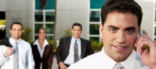Stock Photo: 1598R-214432 Portrait of young Hispanic businessman on cell phone, with other young businesspeople in background