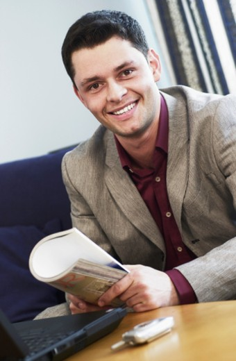 Stock Photo: 1598R-214627 Smiling man holding magazine