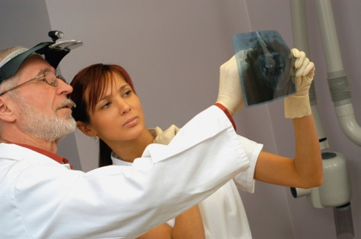 Stock Photo: 1598R-215947 Male dentist and a female dentist examining an X-Ray report