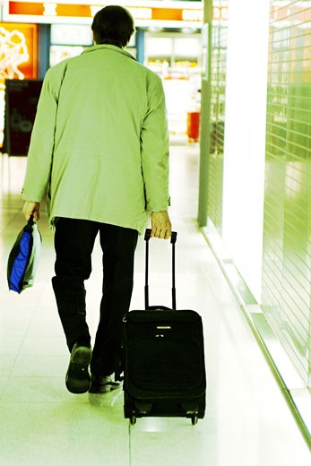 Rear view of a passenger pulling his luggage in an airport : Stock Photo