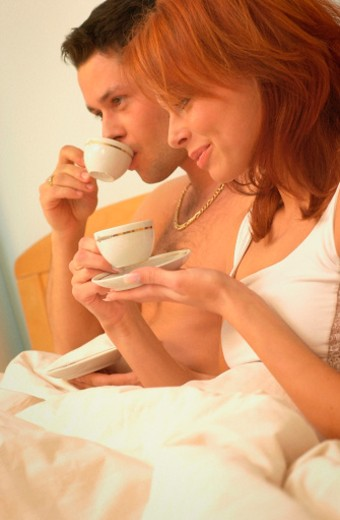 Close-up of a mid adult couple drinking coffee on a bed : Stock Photo