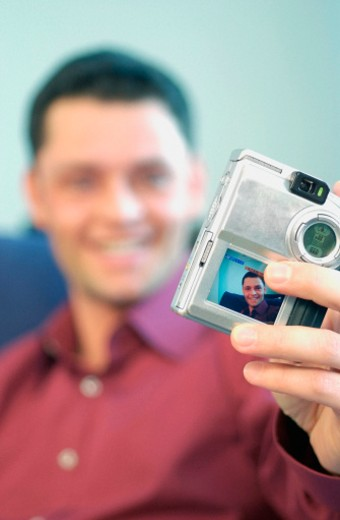 Mid adult man holding a digital camera : Stock Photo